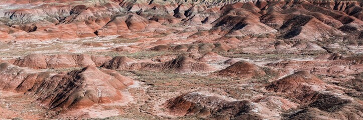 Panoramic view of a vast desert landscape of colorful peaks and hills in shades of red, orange, and purple - the Painted Desert in Arizona