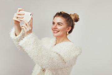 Beautiful joyful woman holding a smartphone and doing selfie