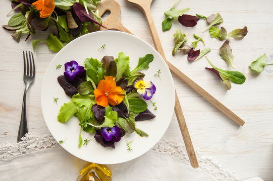 Lettuce and flower salad on woody white background spring, easter
