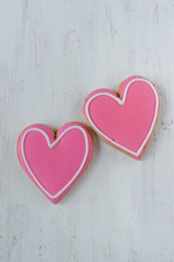 Pink Heart-shaped cookies with icing detail on white background