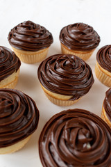 homemade vanilla cupcakes with chocolate swirl icing on white background