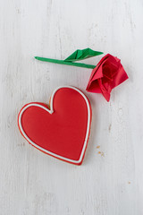 Red Heart-shaped cookie with icing and paper origami red rose on white background