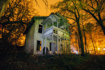 Old creepy wooden abandoned haunted ruined mansion at night