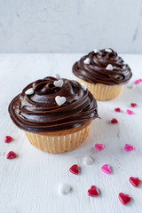homemade vanilla cupcakes with chocolate swirl icing with sprinkle hearts on white background