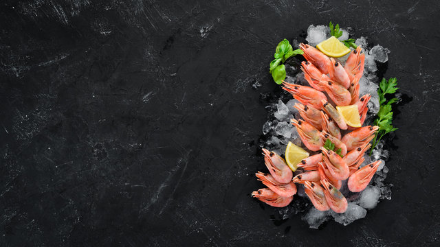 Shrimp with ice and lemon. On the old background. Top view. Free copy space.