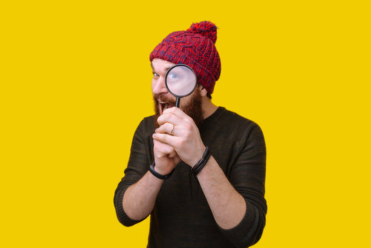 Handsome man with beard and red hat with magnifying glass, funny concept investigation