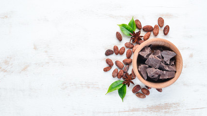 Dark chocolate in a bowl on the old background. Top view. Free copy space.