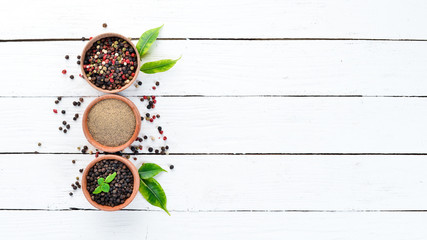 Black pepper, colored pepper, sea salt, ground pepper, dried chili pepper. Top view. On a white background. free space for your text.