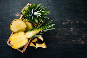 Pineapple. Sliced pineapple on a wooden background. Top view. Free copy space. Wall mural