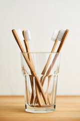 Four bamboo toothbrushes in a glass on a wooden table