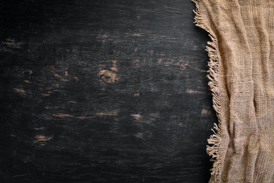 Old linen fabric on a black wooden background.