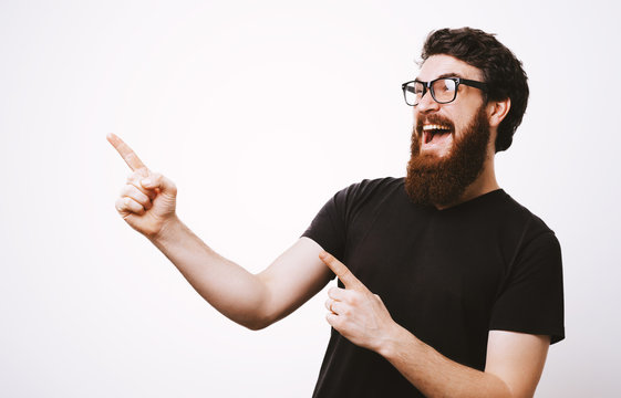 Photo of handsome fancy man wearing black t-shirt having fun and pointing fingers away meaning hey you isolated over white background