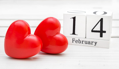 Date of 14 february on cubes with red hearts on white wooden table. Valentine's day.