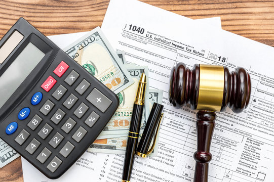Gavel with calculator and money  on tax form. Top view. Tax law.