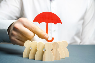 Boss holding a red umbrella and defending his team with a gesture of protection. Life insurance. Customer care, care for employees. Security and safety in a business team. Selective focus Wall mural