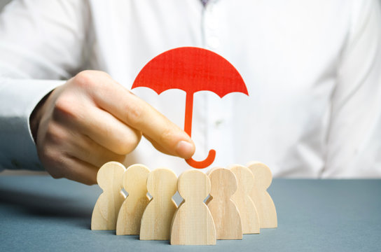 Boss holding a red umbrella and defending his team with a gesture of protection. Life insurance. Customer care, care for employees. Security and safety in a business team. Selective focus