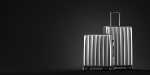 Two silver suitcases on black