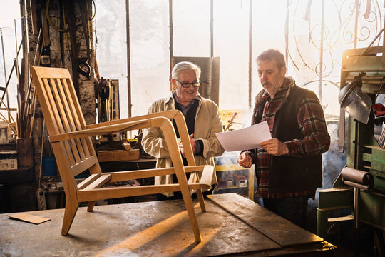 Two craftsmen in their workshop working on an armchair frame