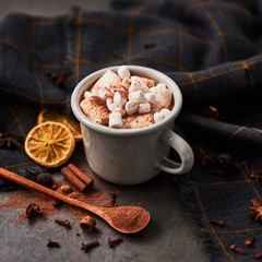 Hot cocoa drink with marshmallows in retro mug surrounded by ingredients: cinnamon, orange, anise and cove on black concrete table. Winter drink. Top view. Rustic look. Copy space. Square crop.