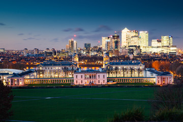 panoramic view from Greenwich on Canary Wharf financial district with skyscrapers at night. View includes the park, National Maritime Museum, Royal chapel and O2