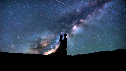 Silhouette of young couple on a milky way stars background. Valentine's day concept.