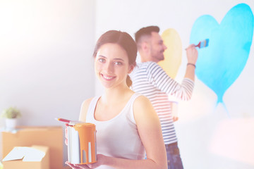 Portrait of happy smiling young couple painting interior wall of new house. young couple