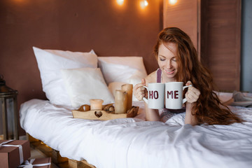 Morning in bed, a young charming red-haired woman with freckles lying in bed, hugging pillow, smiling, enjoying the morning
