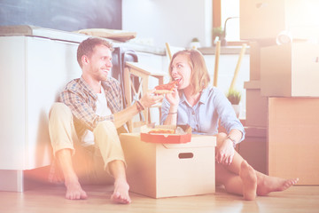 Young couple have a pizza lunch break on the floor after moving into a new home with boxes around them. Young couple