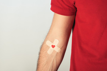 Partial view of patient in red t-shirt with plasters on grey background, blood donation concept Wall mural