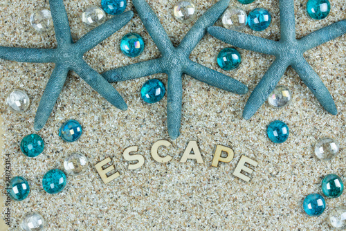 Escape Wooden Letters On A Background Of Sand Teal Blue Starfish