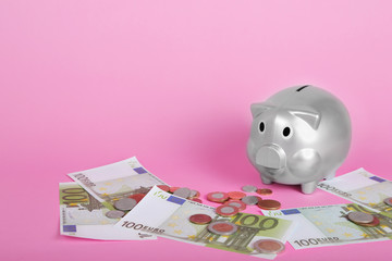 Silver piggy bank , euros banknotes and coins on pink background