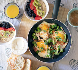 Breakfast with frying eggs juice and berries