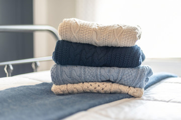 Stack of cable knit sweaters folded on the bed