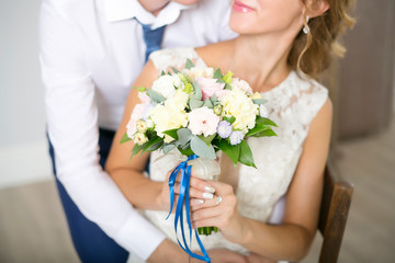 The beautiful wedding bouquet from roses with a blue tape is held in hand by the bride. Husband and wife. Wedding. Wedding day
