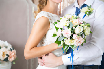 The wife of the husband embraces a wedding bouquet. Newlyweds. Wedding day
