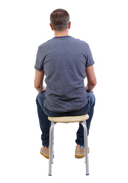 Back view of a man sitting on a chair.