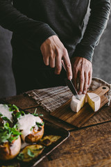 Man's hand cutting cheese on wooden board. Preparation for lunch. Rustic backgraund. Copy space