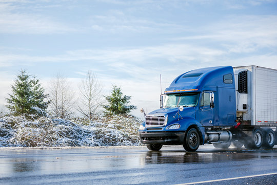 Big rig blue semi truck tractor transporting commercial cargo in refrigerator semi trailer going on the wet road with melting snow with winter snowy trees on the side