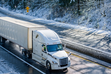 Bright white modern big rig semi truck transporting dry van semi trailer running on winter snowy wet road