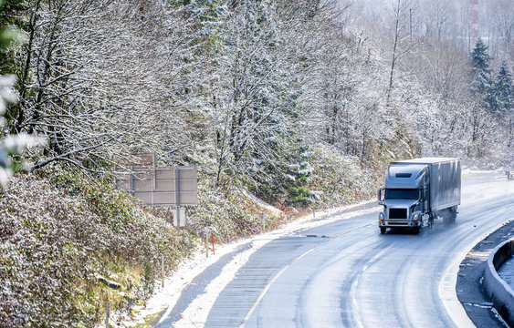 Gray big rig semi truck with covered semi trailer transporting cargo on winter snowing road with wet surface