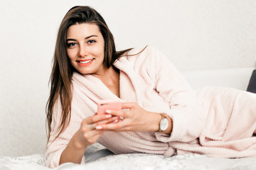 Young smiling woman lying in white bed and using a phone in her bedroom. Happy morning.