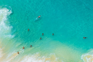 BALI, INDONESIA - 3rd FEB 2019; Aerial view of people swimming in the transparent turquoise sea over sunny day at Kelingking beach. Top view from cliff.