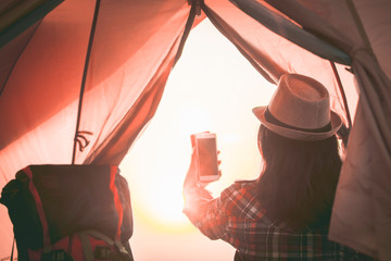 Women tourists take a picture with smartphone after wake up in the morning,view from inside of tent,Sunrise inside a Tent. Camping concept