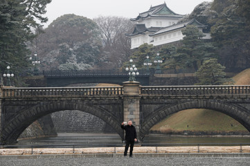 A visitor takes selfie photo at the Imperial Palace as snow falls in Tokyo