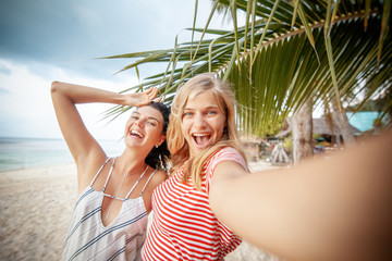 Two happy young beautiful girlfriends laugh make selfie on the background of palm trees and tropical sea, travel and holidays