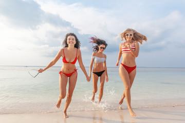0747860e77797 Three beautiful slender happy girlfriends having fun on the beach rejoicing  and having fun against the