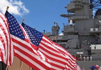 US flags flying beside the Battleship Missouri in Pearl Harbor, Honolulu, Oahu, Hawaii with 4 sailors walking on deck.