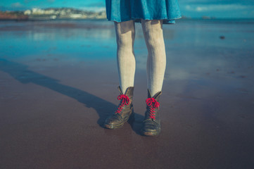 Legs and feet of young woman on the beach in winter