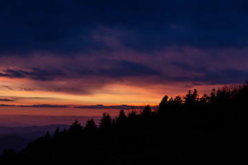 Trees silhouettes against a beautifully colored sky at dusk, with mountains layers in the background