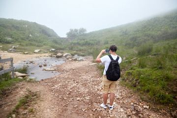 Tourist takes photo of mountain stream  on foggy summer day. Hiking trail in the Pyrenees. La Rhune mountain, France